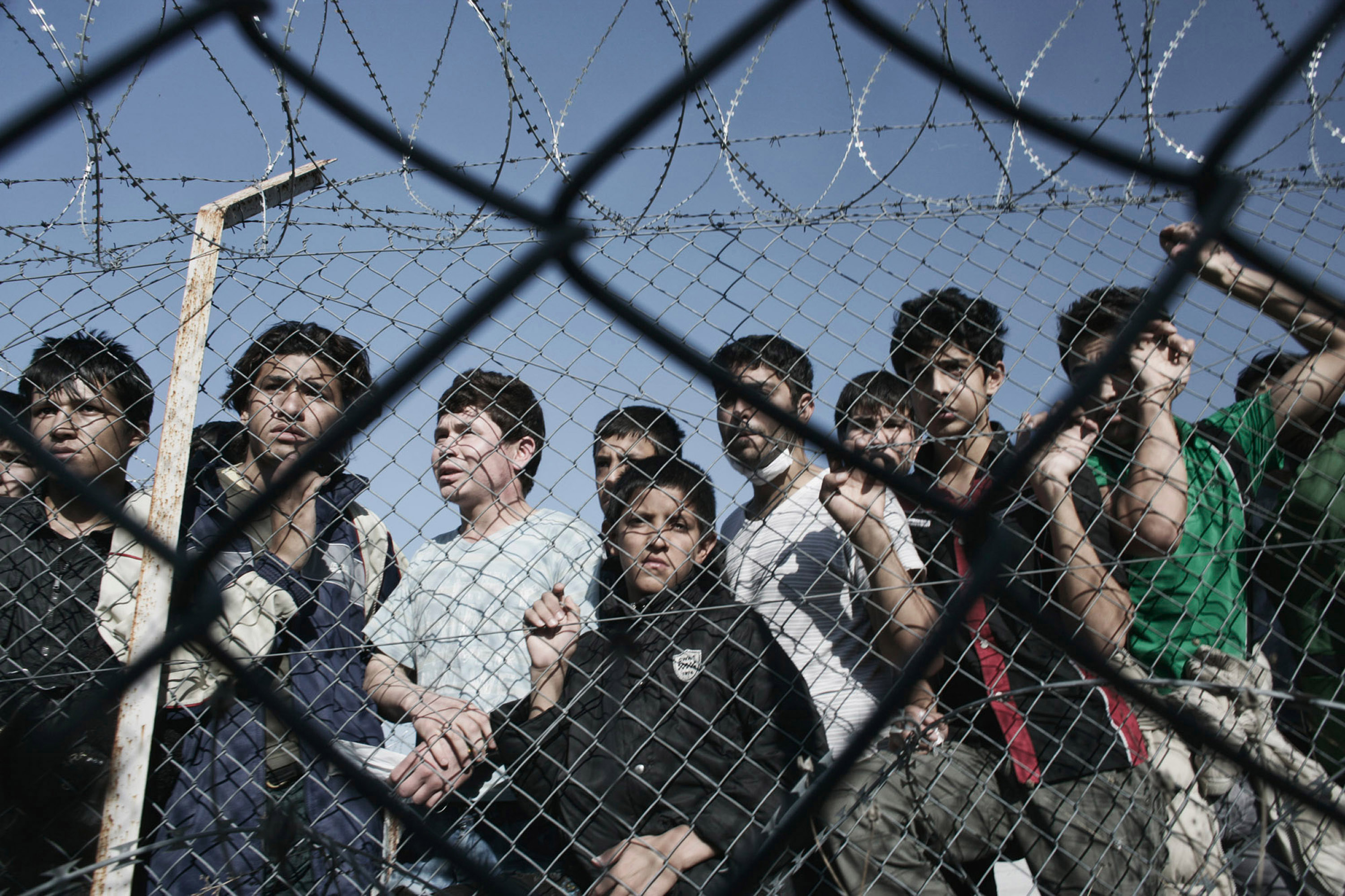 young illegal immigrants standing behind a fence at a detention center, in the Greek village of Filakio near the Greek-Turkish border.