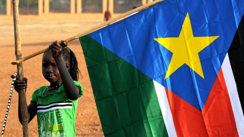 A young girl hangs the South Sudan flag